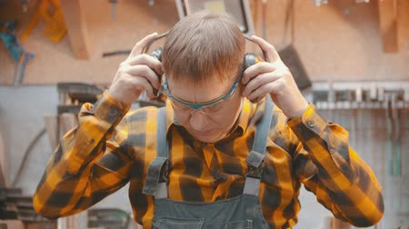 便利屋 : Carpentry indoors - a mature man woodworker put on a protective mask and soundproof headphones 動画素材