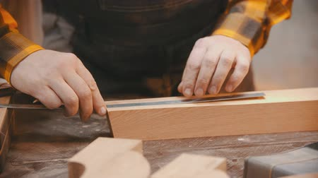 便利屋 : Carpentry indoors - a man woodworker making marks on the wooden detail with a pencil and yardstick