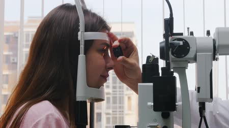eyepieces : Ophthalmology treatment - a young woman checking her visual acuity - pupil reaction to light throw the lens Stock Footage