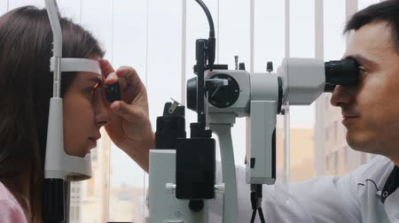 eyepieces : Ophthalmology treatment - a young woman checking her visual acuity with a machine - pupil reaction to light throw the lens - bright cabinet
