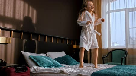 peignoire : A little girl with long hair jumping on the bed of the hotel room