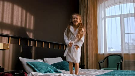 arriving : A happy little girl with long hair jumping on the bed of the hotel room Stock Footage