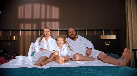 peignoire : A smiling family in white bathrobes sitting in the bed and watching TV - laughing and have fun