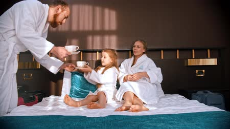 peignoire : A family in white bathrobes in the hotel room - dad brings the tea cups to the bed to his wife and daughter