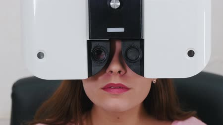 eyepieces : Ophthalmology treatment - a young woman with bright pink lips checking her visual acuity with a special optometry equipment - talking while her eyes are closed with a machine