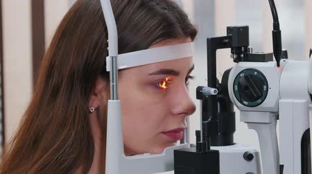 eyepieces : Ophthalmology treatment - a young woman checking her visual acuity with a light of special big optometry machine
