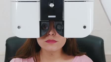 eyepieces : Ophthalmology treatment - a young woman with bright pink lips checking her visual acuity with a special optometry equipment