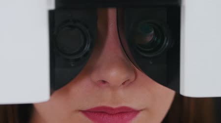 eyepieces : Ophthalmology treatment - a young woman with bright pink lips checking her visual acuity with a special optometry equipment - changing lenses