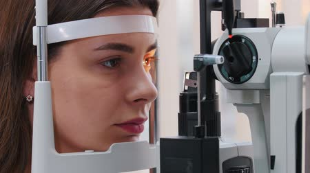 eyepieces : Ophthalmology treatment - a young woman with pink lips checking her visual acuity with a light of special big optometry machine - brown eyes color
