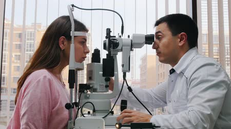 eyepieces : Ophthalmology treatment - a doctor checking young womans visual acuity with a special machine - a spacious cabinet with panoramic window with blinds Stock Footage