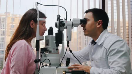 eyepieces : Ophthalmology treatment - a doctor checking young womans visual acuity with a big optometry machine - a spacious cabinet with panoramic window with blinds