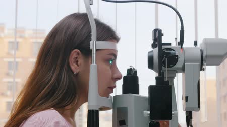 eyepieces : Ophthalmology treatment - a young woman checking her visual acuity - pupil reaction to light Stock Footage