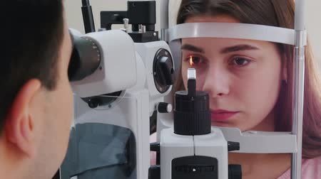 eyepieces : Ophthalmology treatment - a young woman with pink lips checking her visual acuity - pupil reaction to light