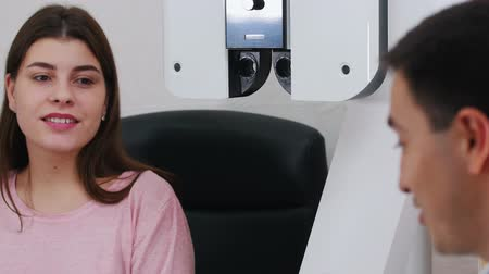 eyepieces : Ophthalmology treatment - a young smiling woman checking her visual acuity with a special big optometry machine then talking about it with a doctor