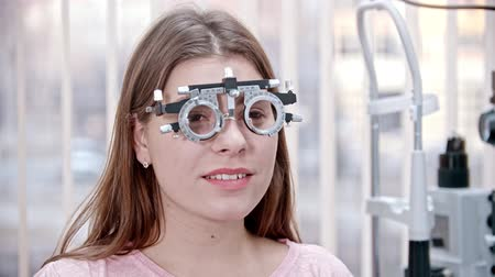 eyepieces : Ophthalmology treatment - a young smiling woman sitting in the optometry device for vision test - reading something