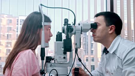 eyepieces : Ophthalmology treatment indoors - a doctor checking young womans visual acuity with a special machine - a spacious cabinet with panoramic window with blinds