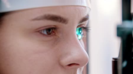 eyepieces : Ophthalmology treatment - a young woman checking her visual acuity - checking a reaction on the green light