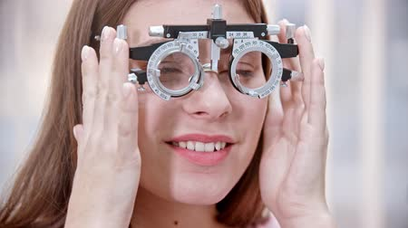 optyk : Ophthalmology treatment - a young smiling woman putting on a device for vision test