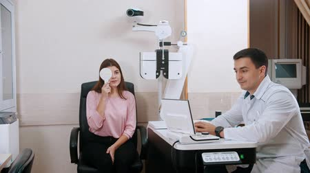 eyepieces : Ophthalmology treatment in the cabinet - young woman checking her visual acuity - closing her eye with an eye shield and reading letters