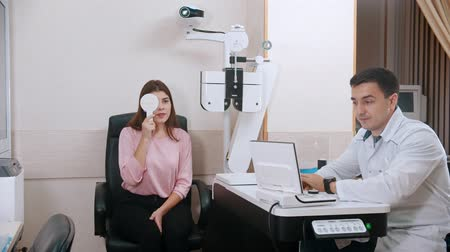 eyepieces : Ophthalmology treatment in the bright cabinet - young woman checking her visual acuity - closing her eye with an eye shield and reading letters
