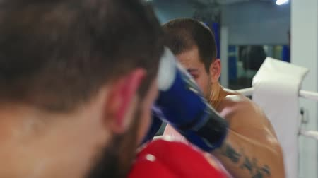 bokser : Box training - two sweaty men with mouth guard having an aggressive fight on the boxing ring