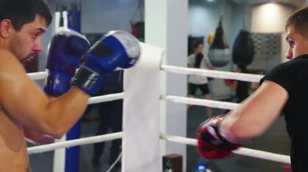 chutando : Boxing in the gym - two men in red and blue gloves having a training fight on the ring