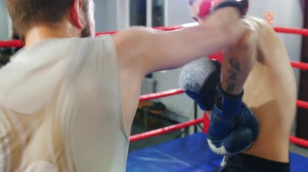 combativo : Boxing training indoors - two men having an aggressive fight on the ring - attack and protect