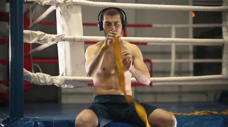 yoğunlaşma : Box training - a man sitting on the ring and bandages his hands Stok Video