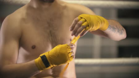narożnik : Box training - a man sitting on the corner of the ring and bandages his hands with an yellow band