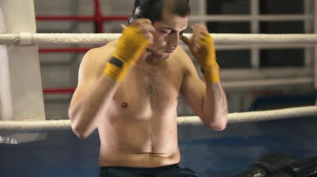 интенсивность : Box training - a man sitting on the ring - putting on headphones and gloves