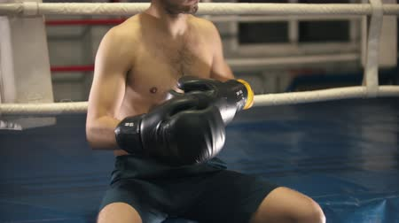stanovena : Box training - a tattooed man sitting on the ring - putting on headphones and gloves Dostupné videozáznamy