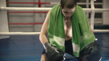boksring : Box training - a tired man sit on the corner of the ring with a towel on the shoulders