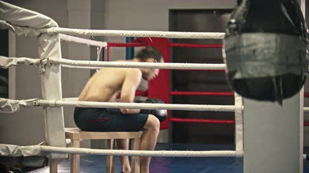 bokser : Box training - a tired man sit on the corner of the ring on the chair