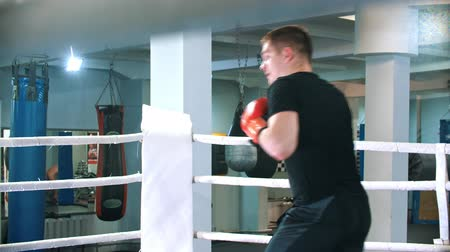 átlyukasztás : BOX - man in black t shirt is boxing with shadow on the ring