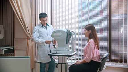 optyk : ophthalmologist - the young woman is sitting at the apparatus of checks eyesight