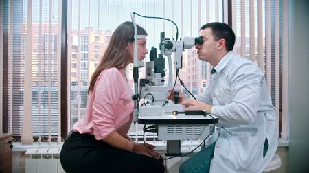 oculista : ophthalmologist - the doctor is checking the eyesight woman in pink cardigan on a special device