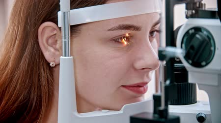 slit : ophthalmologist - glow on the womans eye from a special device Stock Footage