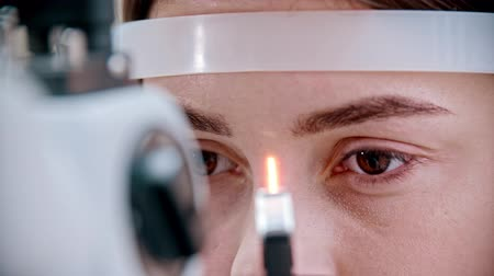slit : ophthalmologist - bright light focused on the beautiful womans eyes Stock Footage