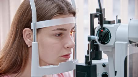 slit : ophthalmologist - woman sitting at an eye test apparatus and waiting Stock Footage