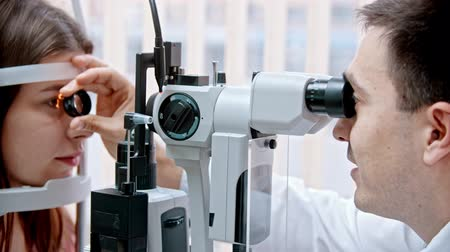 magnifier : ophthalmologist - the doctor is looking at the womans eyesight with a special magnifier Stock Footage