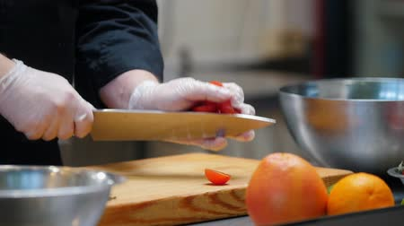 cherry domates : Cooking on modern kitchen - chef cutting cherry tomatoes on the desk Stok Video