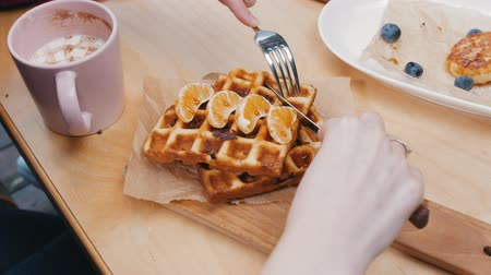 stroop : A young woman pours a syrup on waffles in cafe