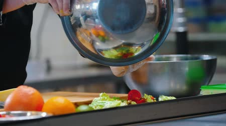 пармезан : KITCHEN - cook transfering vegetables from a metal bowl