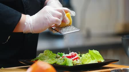 sponka : KITCHEN - cook is rubbing cheese in a grater in a salad