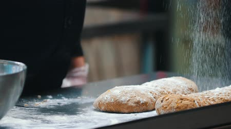 esfregar : KITCHEN - the chef is sprinkling flour on the dough for bread Stock Footage