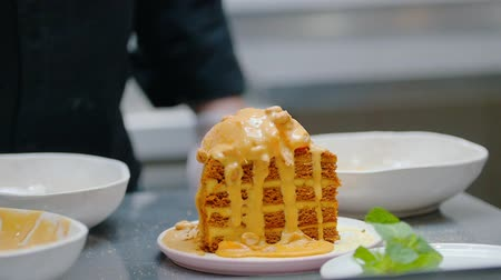 испечь : Restaurant kitchen - Pouring a sweet sauce and granola on the top of honey cake