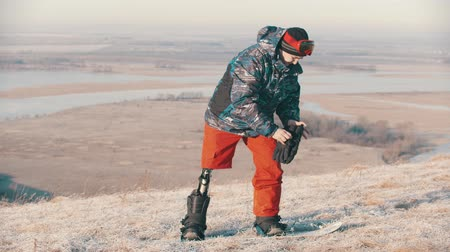 prosthesis : Snowboarding - A man with prosthetic leg standing on the board and putting on the gloves