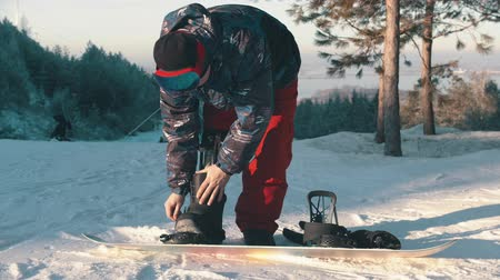 prosthesis : Snowboarding on the mountain - A man with prosthetic leg getting on the board in big boots