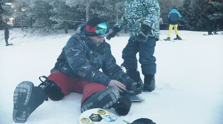 prosthesis : 14-12-19 RUSSIA, KAZAN: Snowboarding - A man with prosthetic leg helps his son to get on the snowboard Stock Footage
