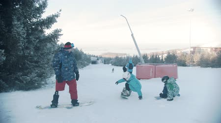 freeride : 14-12-19 RUSSIA, KAZAN: Family snowboarding - A man with prosthetic leg watching his kids trying to get on the snowboard Stock Footage